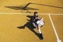 Мужчина баскетболист с помощью смартфона, лежащий на желтой корте после тренировки . — стоковое фото