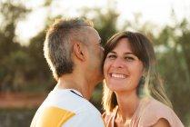 Чоловік цілує дорослу жінку з щасливою усмішкою. — стокове фото
