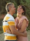 Couple looking at each other with happy smile and laughing at beach — стокове фото