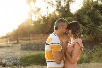 Бічний погляд дорослого чоловіка і жінки, що тримаються за руки і дивляться один на одного з щасливою посмішкою. — стокове фото
