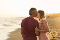 Взрослый мужчина целует женщину на пляже рядом с морем и отдыхает вместе — стоковое фото