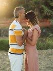 Чоловік тримається за руки і цілує дівчину з щасливою усмішкою. — стокове фото