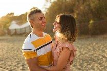 Задоволений дорослий чоловік і жінка сміються і обіймають одне одного, розважаючись на піщаному березі на курорті. — стокове фото
