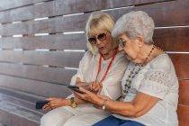 Selbstbewusste, gut gelaunte grauhaarige Seniorinnen in Sommerkleidung und Sonnenbrille sprechen auf einer großen Holzbank — Stockfoto