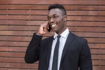 Positive smiling successful African American businessman speaking on mobile phone beside urban striped wooden wall — Stock Photo