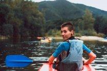Вид сзади спортсменки, оглядывающейся через плечо во время набивки красного каноэ на реке Селла в Испании — стоковое фото