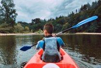 Вид сзади на юную спортсменку в красном каноэ на реке Селла в Испании — стоковое фото
