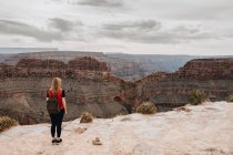 Back view of woman with backpack admiring picturesque view of canyon in USA — Stock Photo