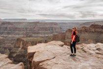 Femme avec sac à dos regardant à la caméra et souriant dans une vue pittoresque du canyon aux États-Unis — Photo de stock