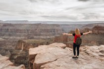 Woman with backpack standing with arms outstretched in picturesque view of canyon in USA — Stock Photo