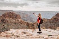 Вид сбоку женщины с рюкзаком, делающей селфи на картинке каньона в США — стоковое фото