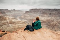 Side view of tranquil woman in jacket with backpack having coffee on rocks and looking at canyon in USA — Stock Photo