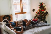 Two friends using laptop and smartphone in bed near Christmas tree in cozy interior. — Stock Photo