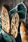 Desde arriba baguettes enteras y a la mitad apetitosas dispuestas en servilleta sobre fondo rústico de madera . - foto de stock