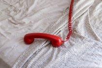 Combiné téléphonique rouge avec fil placé sur un lit doux à la maison — Photo de stock