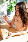 Zufriedene Frau in Sonnenbekleidung beißt glasiertes Gebäck, während sie am Fenster am Tisch sitzt — Stockfoto