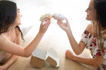 Donne felici in prendisole con scatola di dessert glassati seduti a tavola — Foto stock
