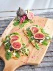 Sandwichs ouverts faits maison avec tranches de figue et fromage sur pain de seigle avec salade de fusée sur planche de bois — Photo de stock