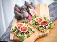 Sandwiches abiertos caseros con rodajas de higo y queso sobre pan de centeno con ensalada de rúcula en tabla de cortar de madera - foto de stock