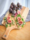 Homemade open sandwiches with slices of fig and cheese on rye bread with rocket salad on wooden cutting board — Stock Photo