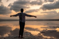 From behind man in wet clothes gazing and standing with outstretched arms with empty fish tank at coast in cloudy sunset — Stock Photo