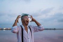 Verzweifelter Mann in Todesangst in nassem Hemd mit leerem Aquarium auf dem Kopf, schreiend am stillen Meer in der Dämmerung — Stockfoto
