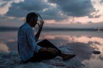 Страшный мужчина в мокрой рубашке, вынимающий пустой аквариум, сидя на берегу моря в сумерках — стоковое фото