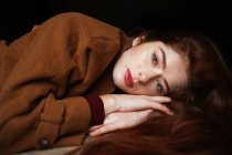 Charming thoughtful woman in brown coat lying on hands and dreaming while looking in camera — Stock Photo