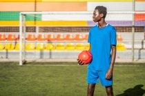 Черный футболист с мячом, стоящим на стадионе и смотрящим в сторону — стоковое фото