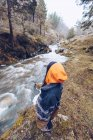 From above woman in warm jacket standing by furious torrent at evergreen forest on cold autumn daytime — Stock Photo