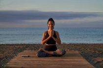 Позитивная женщина со скрещенными ногами и сжатыми руками, улыбающаяся и медитирующая, сидя вечером на берегу моря — стоковое фото