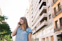 Blonde young cheerful female with sunglasses in blue T-shirt standing on street of city and talking on smartphone — Stock Photo