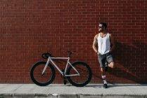 Расслабленный современный велосипедист в спортивной одежде и солнцезащитных очках, отдыхающий рядом с велосипедом, стоя на одной ноге и опираясь спиной и ногами на красную кирпичную стену — стоковое фото