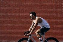 Современный велосипедист в спортивной одежде и солнцезащитных очках на велосипеде возле стены из красного кирпича — стоковое фото