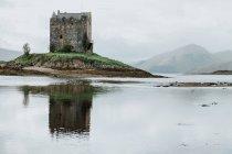 Antiguo edificio del castillo situado en una pequeña isla cerca de las montañas de Escocia - foto de stock