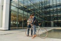 Alegre hombre y mujer con la bicicleta sonriendo y mirando una tableta mientras se comunica fuera del edificio de oficinas en la calle de la ciudad moderna - foto de stock