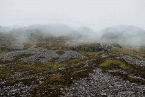 Paysage sauvage de collines rocheuses couvertes par une épaisse brume en Écosse — Photo de stock
