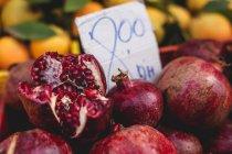 Stand pieno di melograni biologici maturi con cartellino del prezzo al mercato agricolo all'aperto — Foto stock