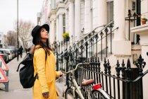 Giovane donna in cappotto giallo alla moda ammirando edifici ornamentali mentre si trova sulla strada asfaltata di Londra, Regno Unito — Foto stock
