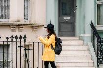 Vista lateral da senhora em casaco amarelo moderno e smartphone de navegação de chapéu enquanto caminhava perto da casa miserável na rua de Londres, Reino Unido — Fotografia de Stock