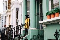 Щаслива стильна жінка в жовтому пальто і капелюсі посміхається, стоячи на сходах у будинку на вулицях Лондона, Велика Британія. — стокове фото