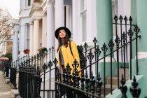 Joyeux élégant femme en manteau jaune et chapeau souriant tout en se tenant dans les escaliers dans une maison dans les rues de Londres, Royaume-Uni — Photo de stock