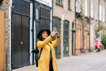 Woman in yellow coat and hat using smartphone to take picture of old building on street of London, United Kingdom — Stock Photo
