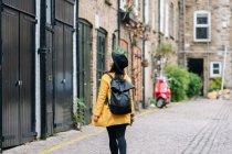 Rückansicht einer Frau in gelbem Mantel und Hut, die an einem alten Gebäude auf der Straße von London, Vereinigtes Königreich, vorbeigeht — Stockfoto