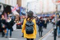 Rückansicht einer Frau in gelbem Mantel und stylischem Hut, die während des Karnevals in London unterwegs ist, Vereinigtes Königreich — Stockfoto