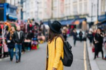 Side view of woman in yellow coat and stylish hat walking on road during carnival in London, United Kingdom — Stock Photo