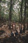 Jovem mulher calma em chapéu elegante e cachecol sentado no chão com os olhos fechados e descansando na floresta verde — Fotografia de Stock