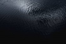 From above abstract texture of dark gray wavy water reflecting clouds in Chile — Photo de stock