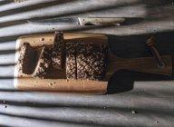 Pão integral fatiado em tábua de corte de madeira na mesa com sombra — Fotografia de Stock