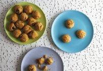 Galletas marrones frescas con migas en platos de cerámica de colores en la mesa en la cocina - foto de stock